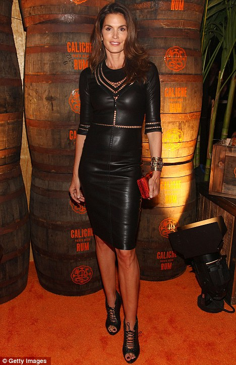 Supermodel Cindy Crawford woos the crowd in a black leather dress and lace-ups