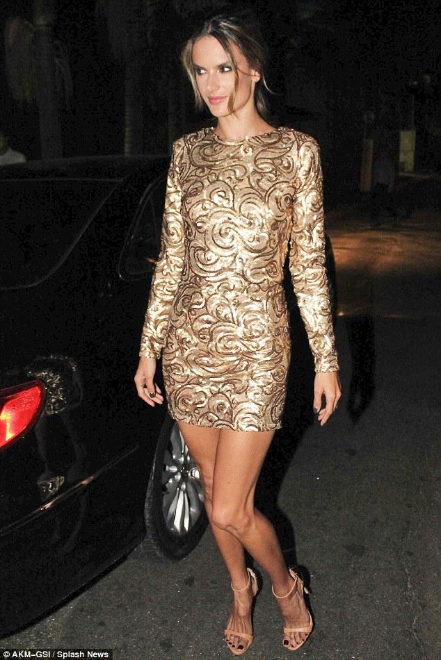 Alessandra Ambrosio shines in gold colored dress