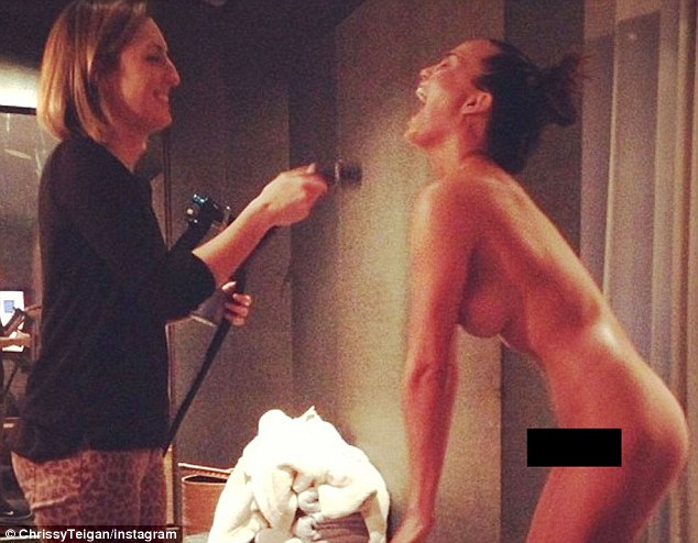 Chrissy Teigen gets sprayed on!