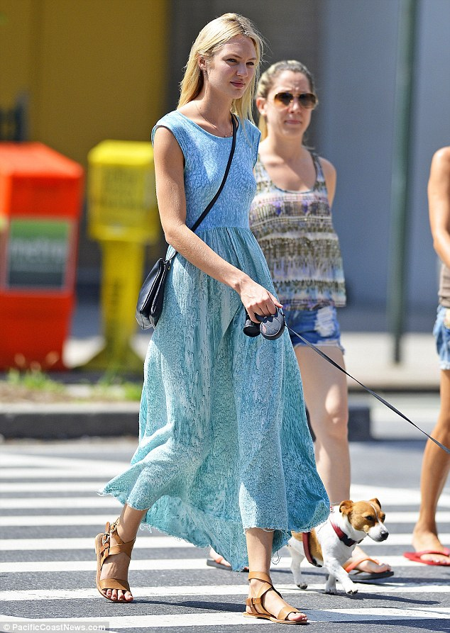 Candice Swanepoel covers up for a walk with the dog