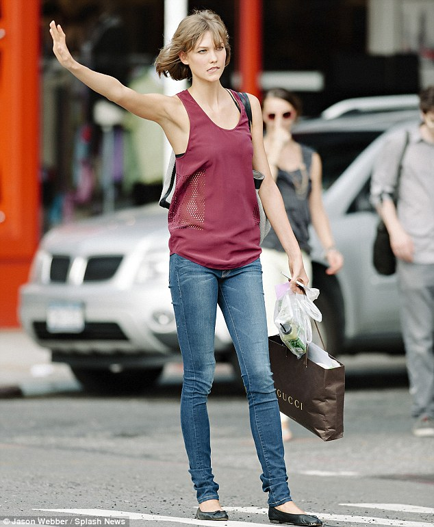 Karlie Kloss tries hailing a cab in busy New York City