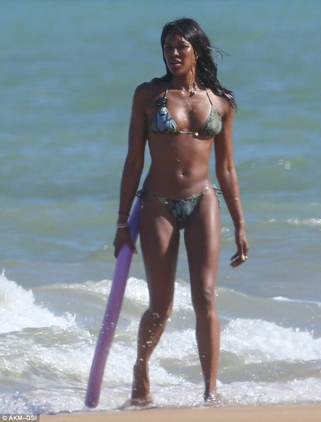 Naomi Campbell soaks up the Brazilian sun in snake pattern swimsuit